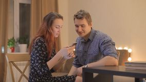 Young couple looks at the phone at home stock video footage