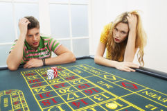 Young Couple Losing On Roulette Table. Young men and women losing on roulette table royalty free stock photography