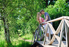 Young couple in love. Young couple on wooden bridge among trees Stock Photography
