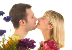 Young couple in love. Kissing in front of flowers royalty free stock photo