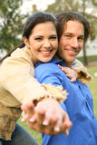 Young Couple In Love. Happy couple holding hand to camera and smiling showing love and sharing royalty free stock image