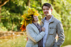 Young couple in love with autumn maple leaves in park at fall ou Stock Images
