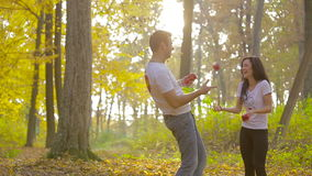 Young couple in love in autumn park. Men and women play with apples stock video