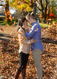 Young couple in love in an autumn setting with leaves falling ar Royalty Free Stock Images