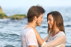 Young couple in love bathing in the sea. Profile of a young couple in love bathing in the sea in the beach royalty free stock photography