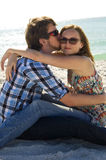 Young couple in love on beach. A young couple sitting face to face on the beach.  The guys kissing the girls cheek Stock Photo