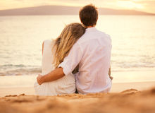 Young couple in love on the beach sunset Stock Image