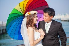 Young couple in love. Beautiful asian couple on the beach in wedding dress Stock Photo