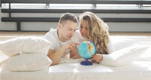 Young couple in love in bed are looking at globe choosing a place to travel on honeymoon. stock video footage