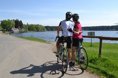 Couple in love on spring bike ride. Young couple in love on bikes riding during beautiful spring day and looking at the azure lake stock image