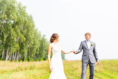 Young couple in love bride and groom posing in a field with yellow grass  in their wedding day in the summer Stock Photo