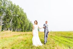 Young couple in love bride and groom posing in a field with yellow grass  in their wedding day in the summer Royalty Free Stock Photos