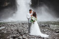 Young couple in love bride and groom, wedding day near a mountain waterfall. Enjoy a moment of happiness and love. Bride in a luxurious wedding dress royalty free stock photo
