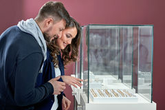 Young couple in love buying rings at the jewelry store. Aiming for the best one on display. Happy beautiful couple choosing an engagement ring on a display of a royalty free stock image