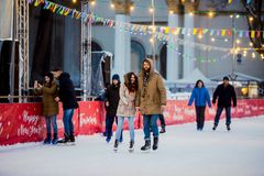 Young couple in love Caucasian man with blond hair with long hair and beard and beautiful woman have fun, active date skating on i stock images