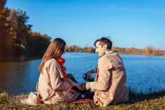 Young couple in love chilling by autumn lake. Happy man and woman enjoying tea outdoors stock photography