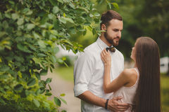 A young couple in love in the city Park in the summer. A young couple, a men of Caucasian appearance, with short hair and a beautiful beard, white shirt and bow royalty free stock image