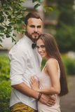 A young couple in love in the city Park in the summer. A young couple, a men of Caucasian appearance, with short hair and a beautiful beard, white shirt and bow stock photos