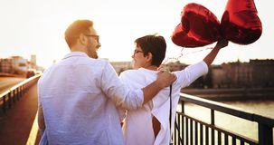 Young couple in love dating and smiling outdoor. While holding heart baloons Royalty Free Stock Image