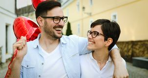Young couple in love dating and smiling outdoor. While holding heart baloons Stock Photos