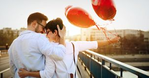 Young couple in love dating and smiling outdoor. While holding heart baloons royalty free stock photo