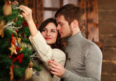 Young couple in love decorates Christmas tree at home Stock Images
