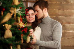 Young couple in love decorates Christmas tree at home Royalty Free Stock Image