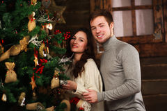 Young couple in love decorates Christmas tree at home Stock Photography