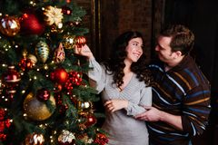 Young couple in love decorates a Christmas tree at home. Couple in love decorates a Christmas tree at home. loft interior brick walls. Embrace, kiss, hang toys Stock Image