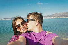 Young couple in love doing self-portrait on beach. Happy young couple in love doing self-portrait on background of blue sea and men kissing a woman Stock Photography