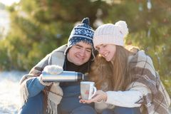 Young couple in love drink a hot drink from a thermos, sitting in the winter in the forest, tucked into warm, comfortable rugs,