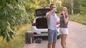 Couple drinking coffee and relaxing on the roadside during a car trip in summer. A young couple in love drinking tea or coffee from a thermo cups standing near stock video