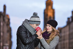 Young couple in love embracing and drinking hot drink from red c Royalty Free Stock Photography
