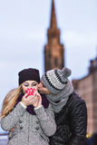 Young couple in love embracing and drinking hot drink from red c Stock Photo