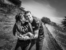 Happy young romantic couple in love embracing and kissing in a field. royalty free stock photo