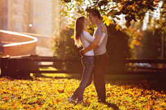 Young couple in love, embracing on sunset in the park Royalty Free Stock Photo