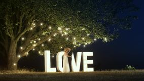 Young couple in love in evening dresses are dancing near love light letters. stock images