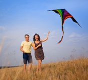 Young couple in love with flying a kite at countryside. Happy young couple in love with flying a kite at countryside stock photo
