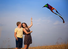 Young couple in love with flying a kite at countryside. Happy young couple in love with flying a kite at countryside royalty free stock photos
