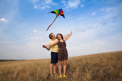 Young couple in love with flying a kite at countryside. Happy young couple in love with flying a kite at countryside royalty free stock image