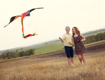 Young couple in love with flying a kite at countryside. Happy young couple in love with flying a kite at countryside royalty free stock photo