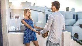 Young couple in love, girl looks at man, hold hands. Blonde beautiful women smiles coquettishly. First date, acquaintance,. Marriage proposal, honeymoon. Summer royalty free stock photos