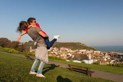 Young couple in love on a green hill, fun, hug Stock Photo