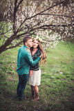Young couple in love having a date under pink blossom trees. Royalty Free Stock Image