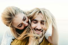 A young couple in love having fun and playing with a hair of the girl. A cheerful bride and groom laughing, close-up Royalty Free Stock Image