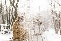 Blowing away snow. Young couple in love having fun on a snowy winter day, blowing away and throwing snow stock photo