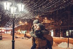 Young couple having fun under holiday winter illumination at night. Young couple in love having fun under holiday winter illumination at night Stock Photography
