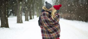 Couple wrapped in blanket outdoors Royalty Free Stock Image