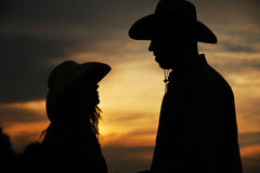 Young couple in love on haystacks in cowboy hats Stock Photography
