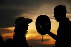 Young couple in love on haystacks in cowboy hats Royalty Free Stock Photos